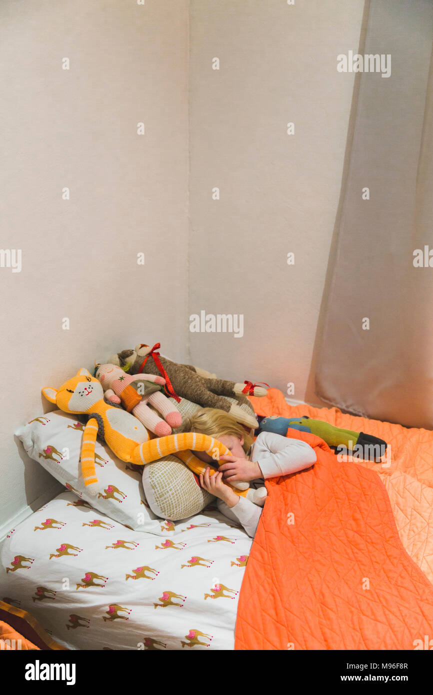 Girl hiding in bed behind stuffed animals - Stock Image