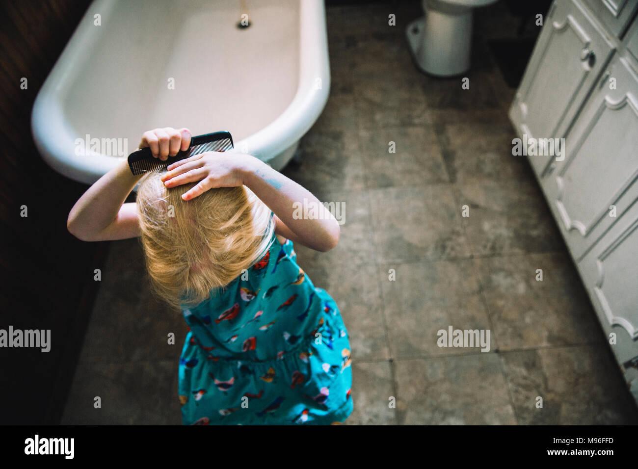 Girl combing her hair Stock Photo