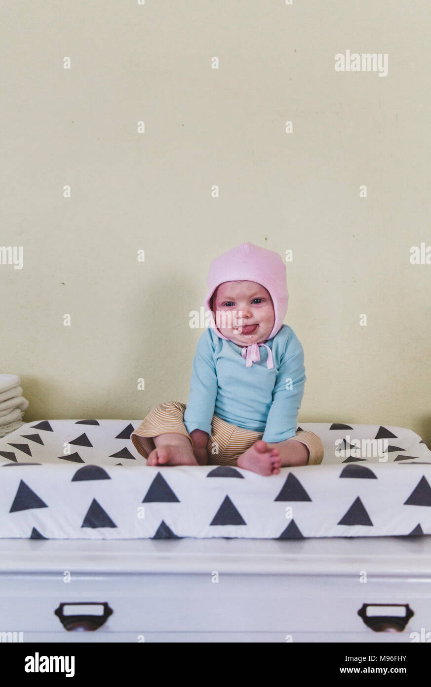 Baby with pink bonnet laughing on bed - Stock Image