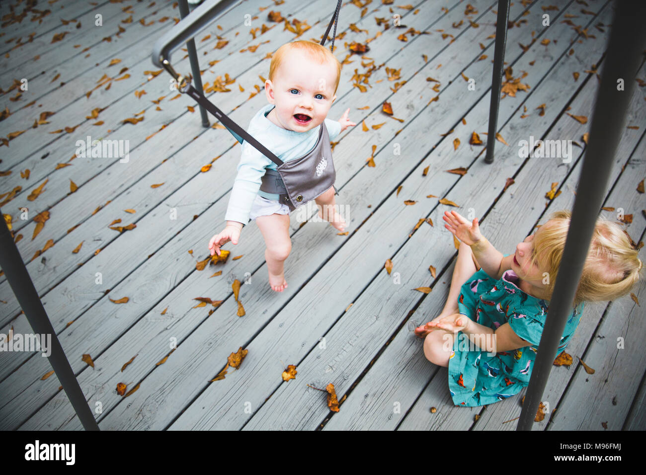 Baby smiling and jumping with girl watching - Stock Image