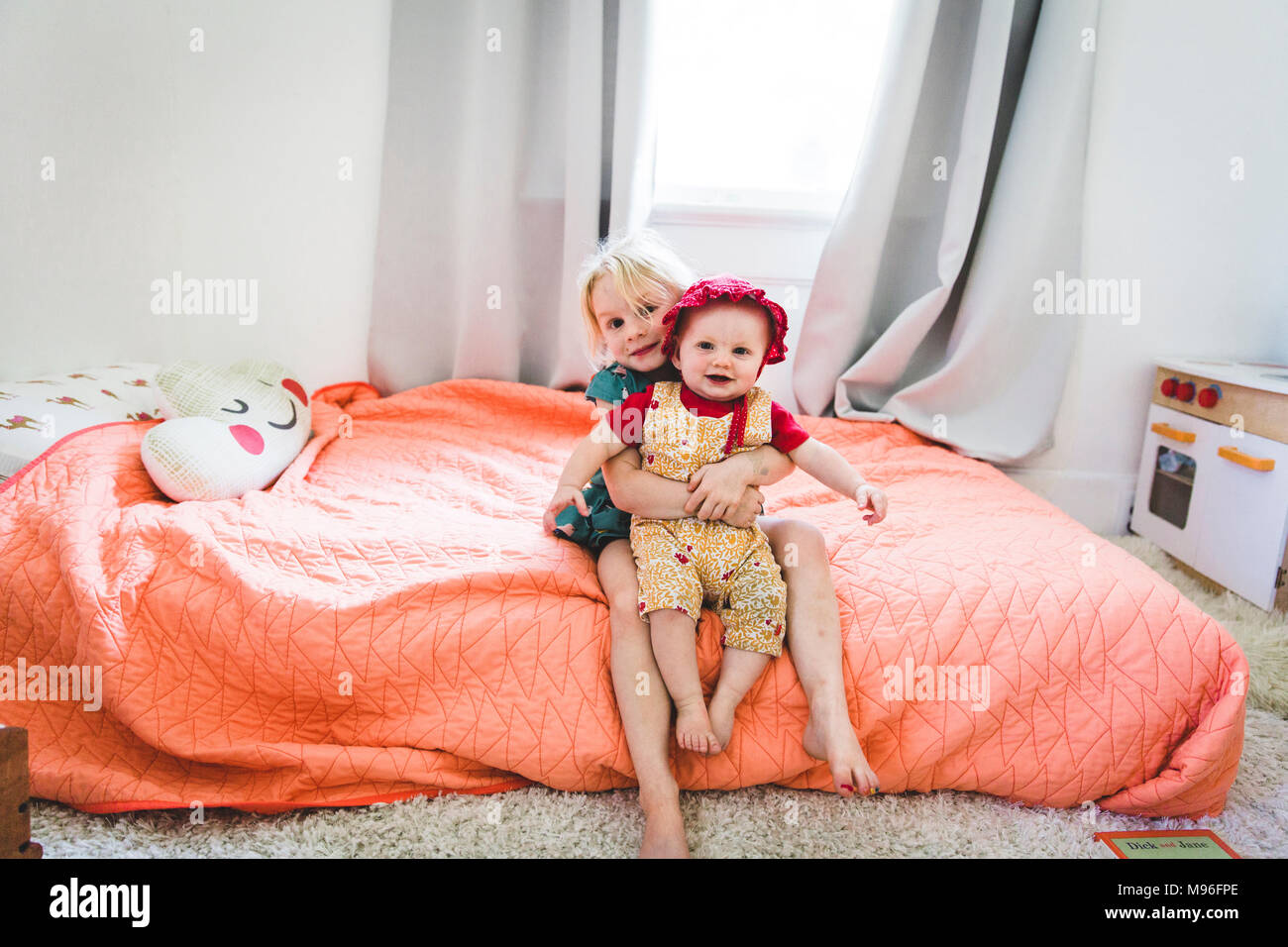 Girl holding baby on bed - Stock Image