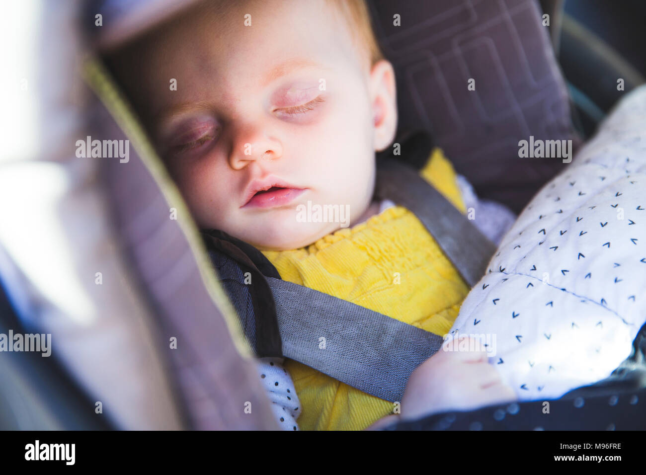Child asleep in car seat - Stock Image