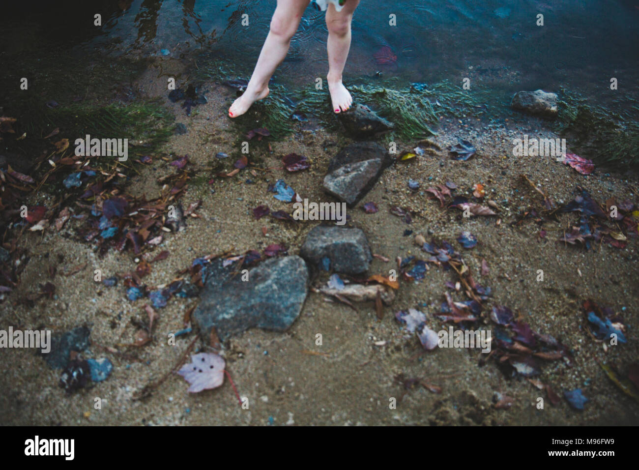 Child on rocky sand - Stock Image