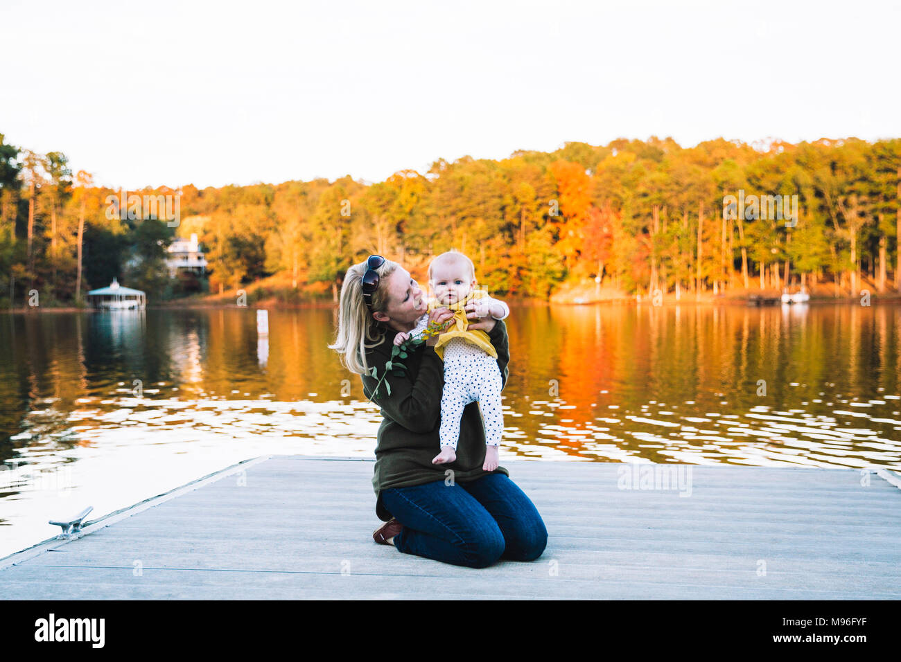 Woman holding baby on dockside - Stock Image