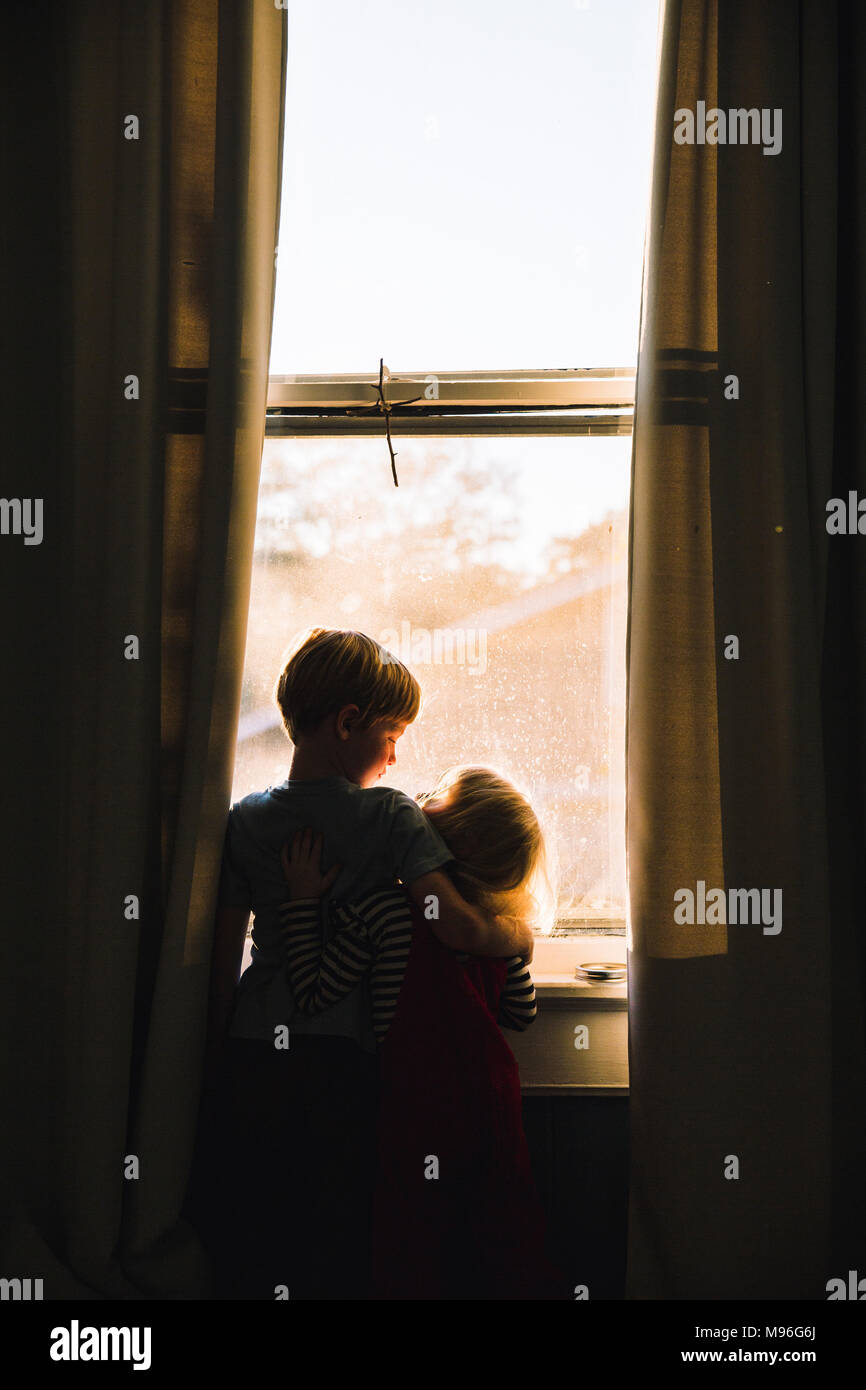Children hugging next to dim window space - Stock Image