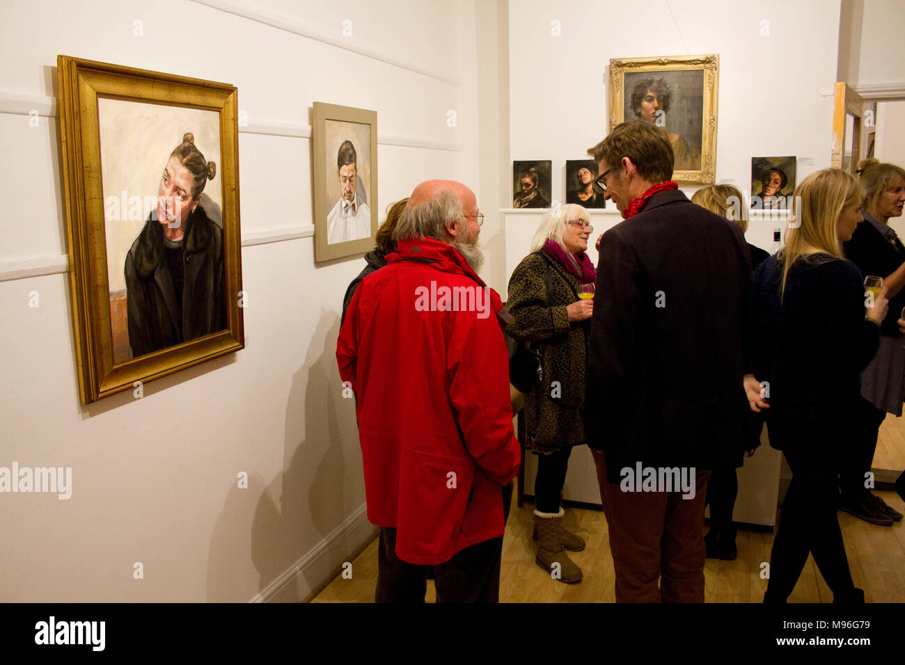 People socialise at a private view of portrait paintings - Stock Image
