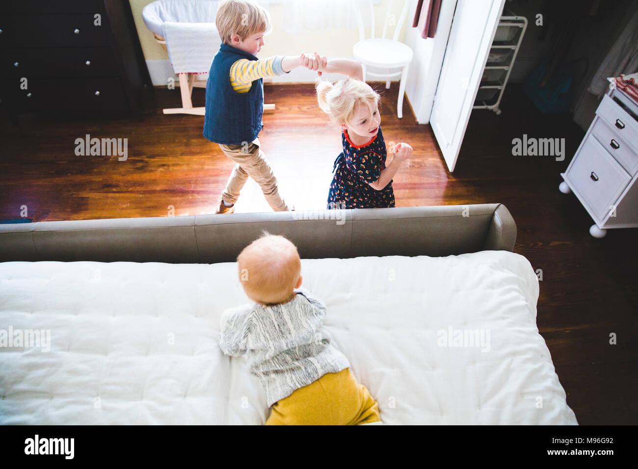 Children playing around bed - Stock Image