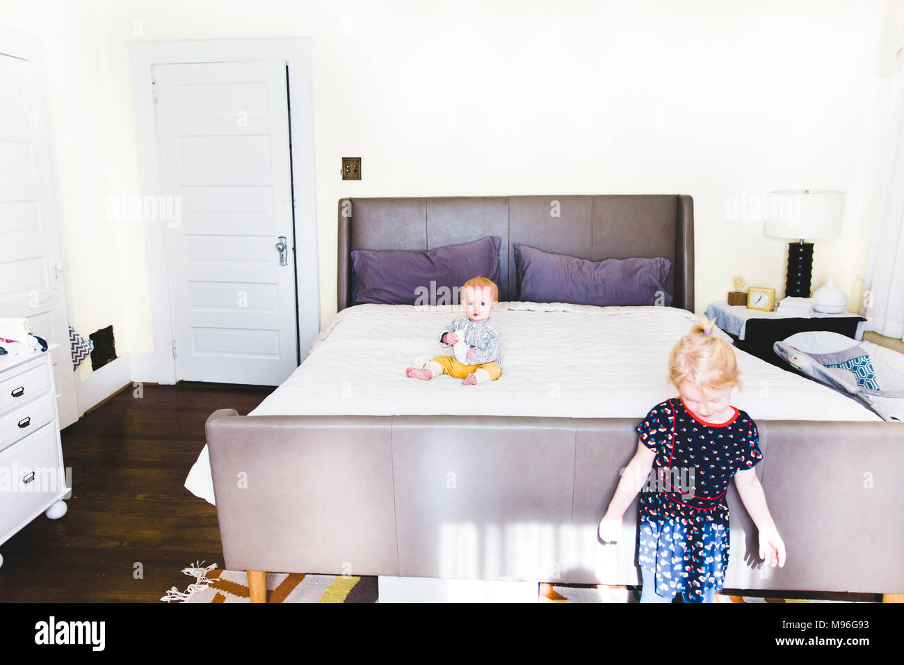 Baby sitting on bed with girl in foreground - Stock Image
