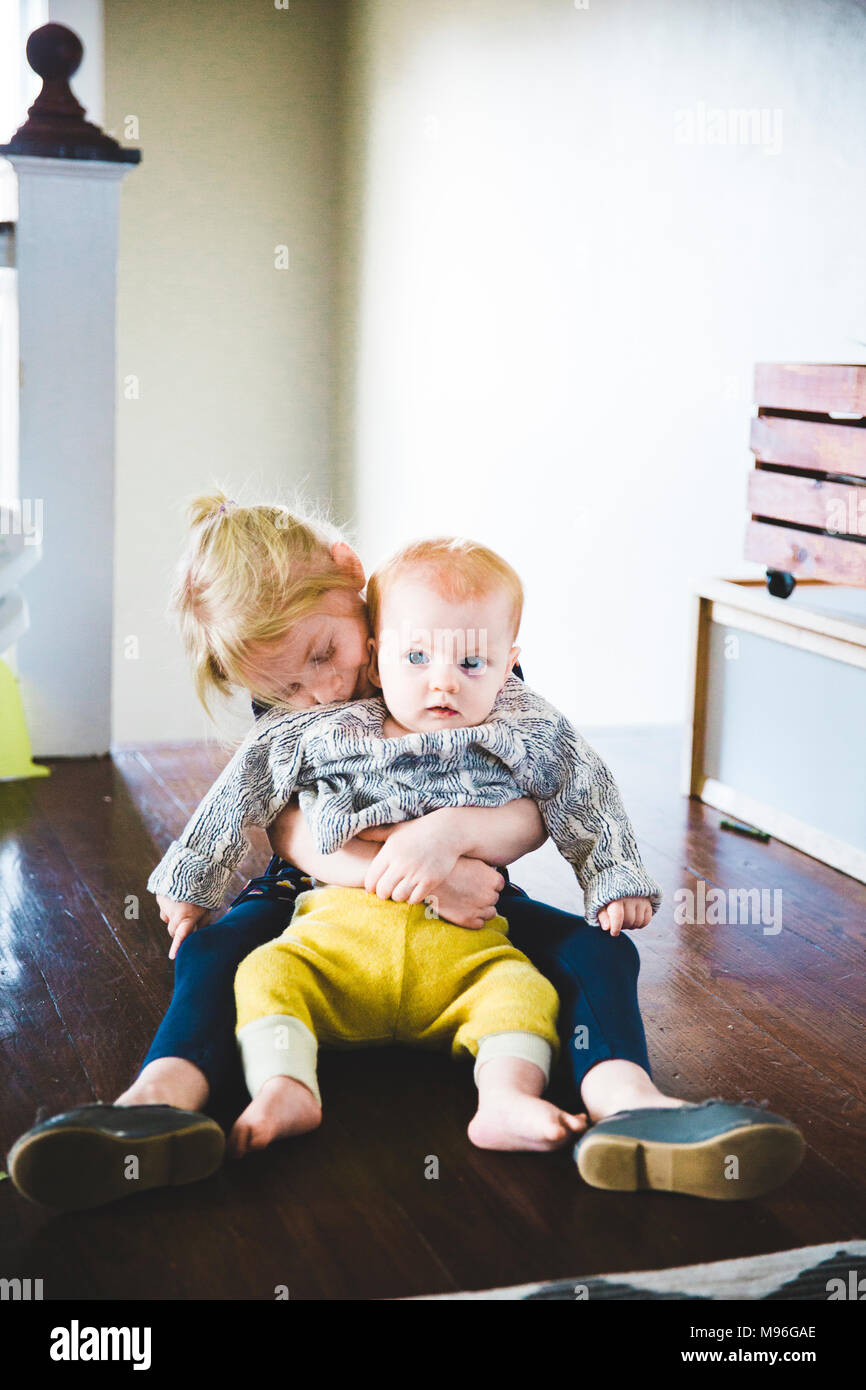 Baby sitting on girl's lap being hugged - Stock Image
