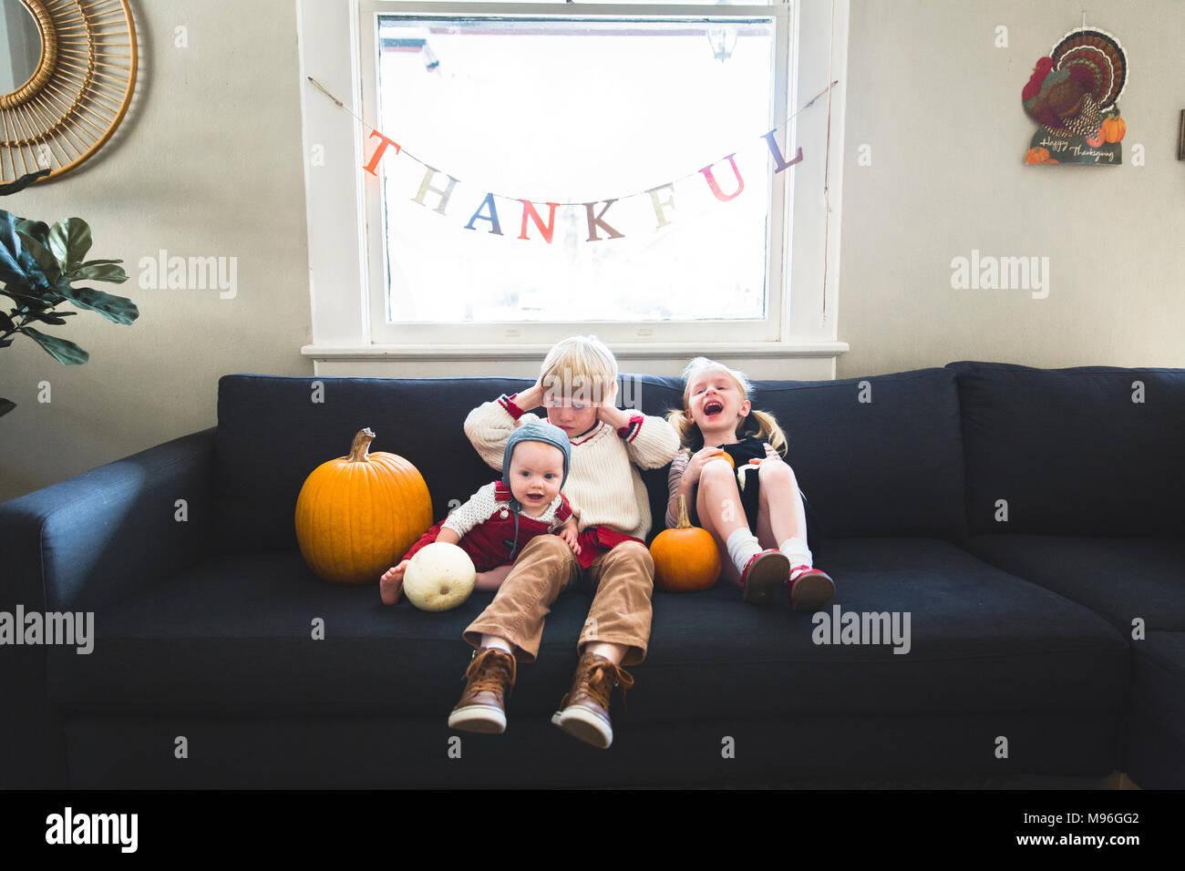 Children sitting underneath thankful banner with pumpkins - Stock Image