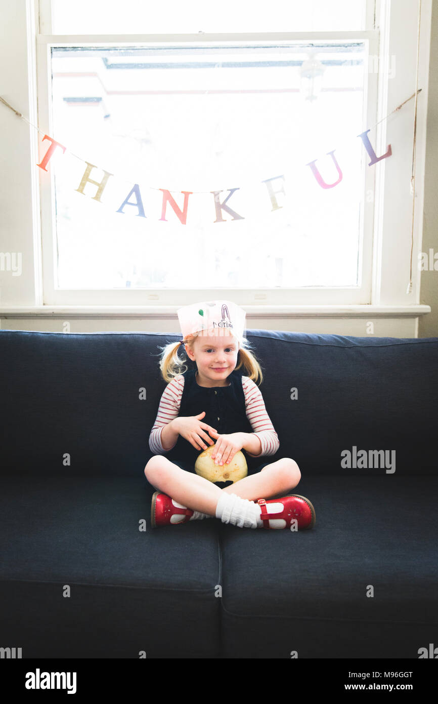 Girl sitting underneath thankful banner - Stock Image