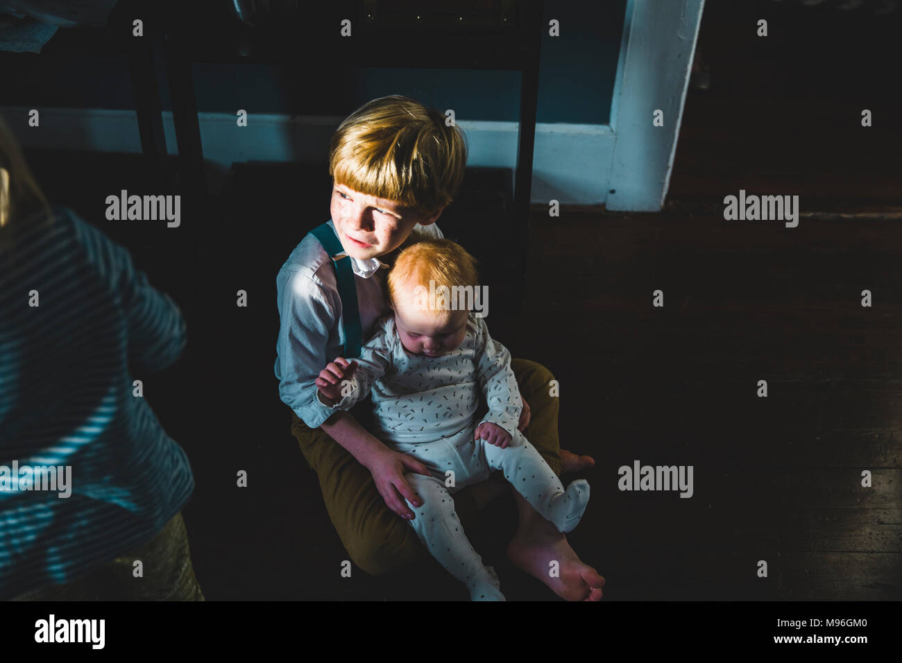 Baby sitting on boy's lap - Stock Image