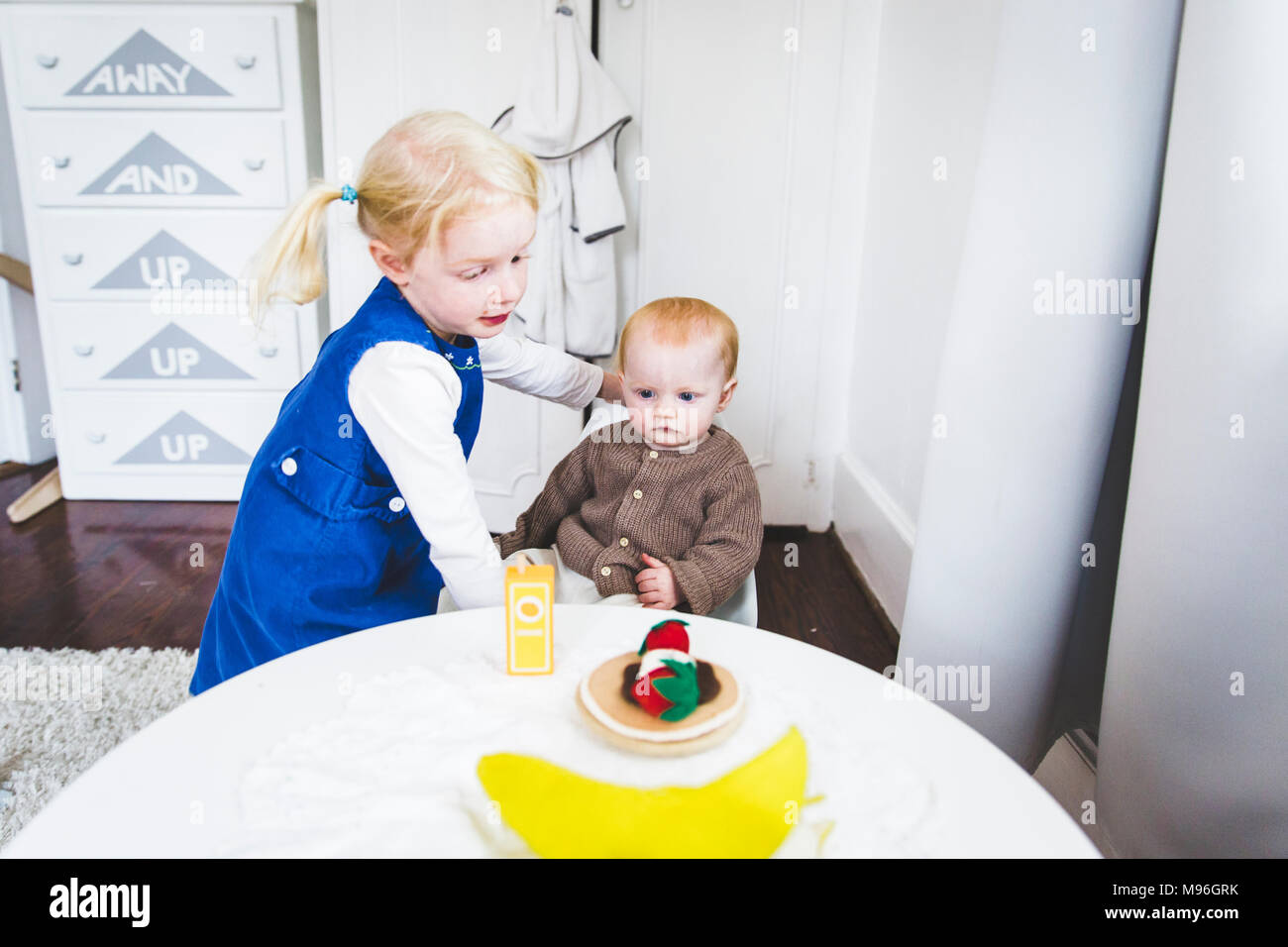 Girl helping baby at table - Stock Image