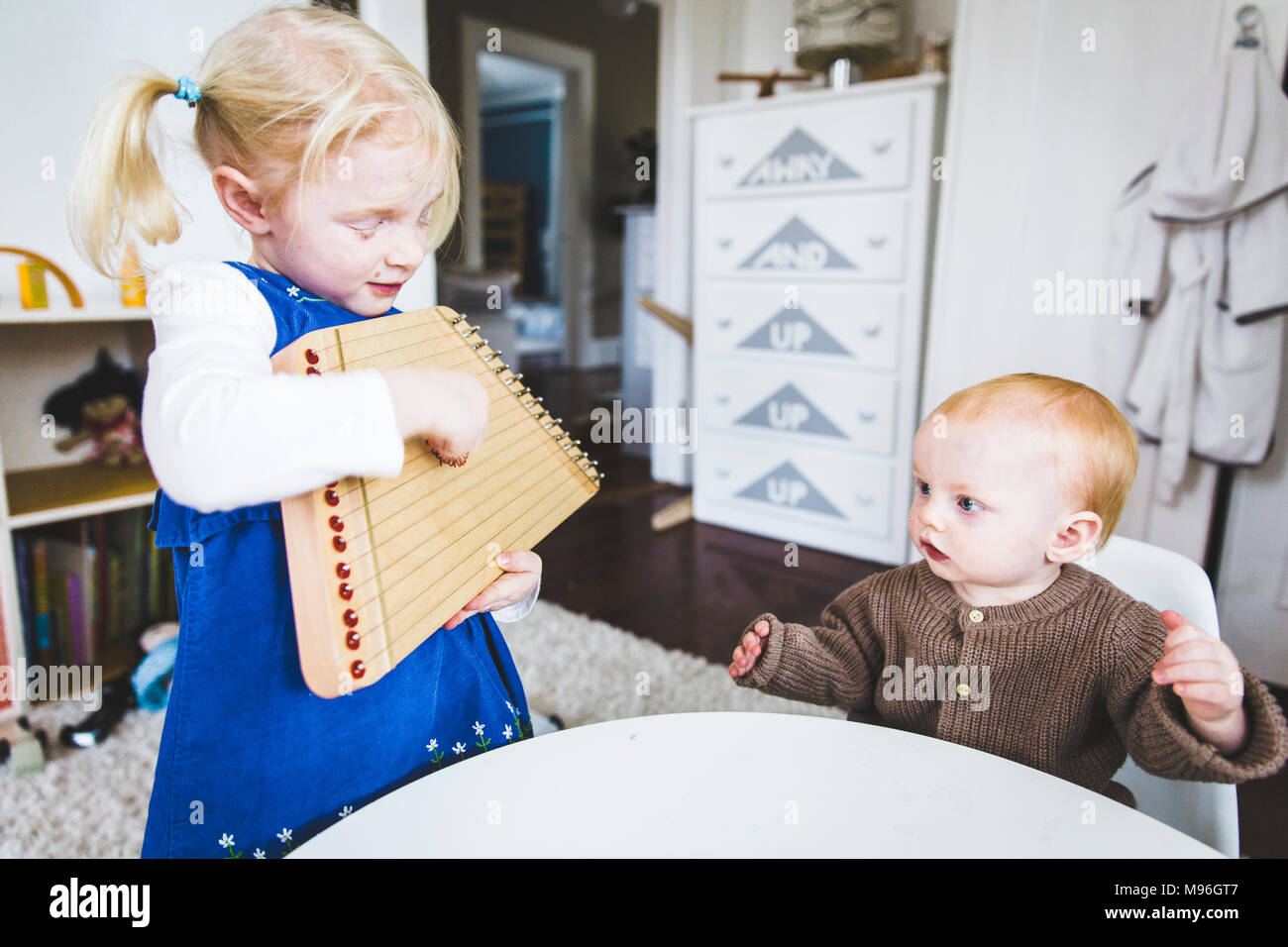 Girl playing harp in front of baby - Stock Image