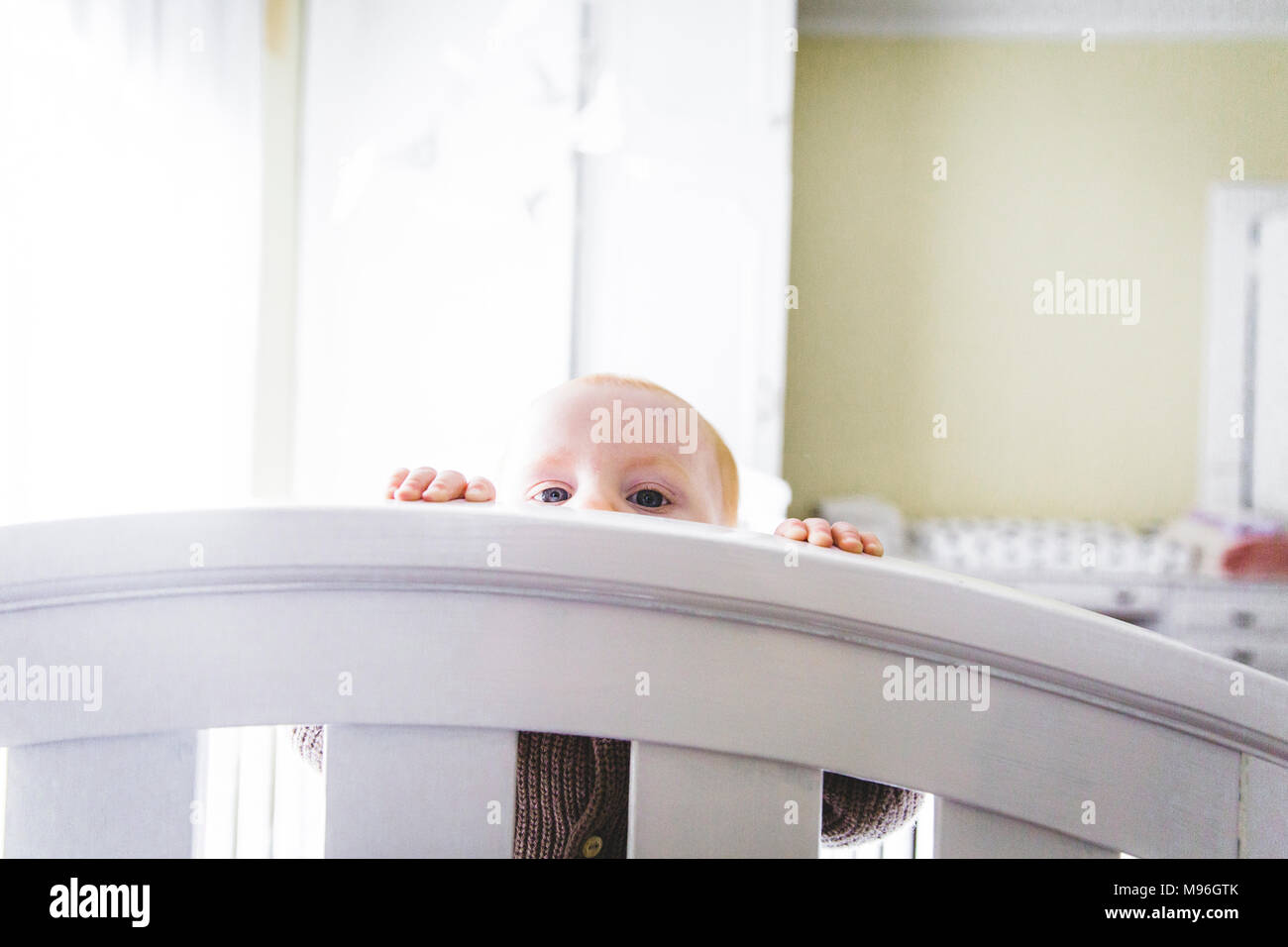 Baby peering over bed - Stock Image
