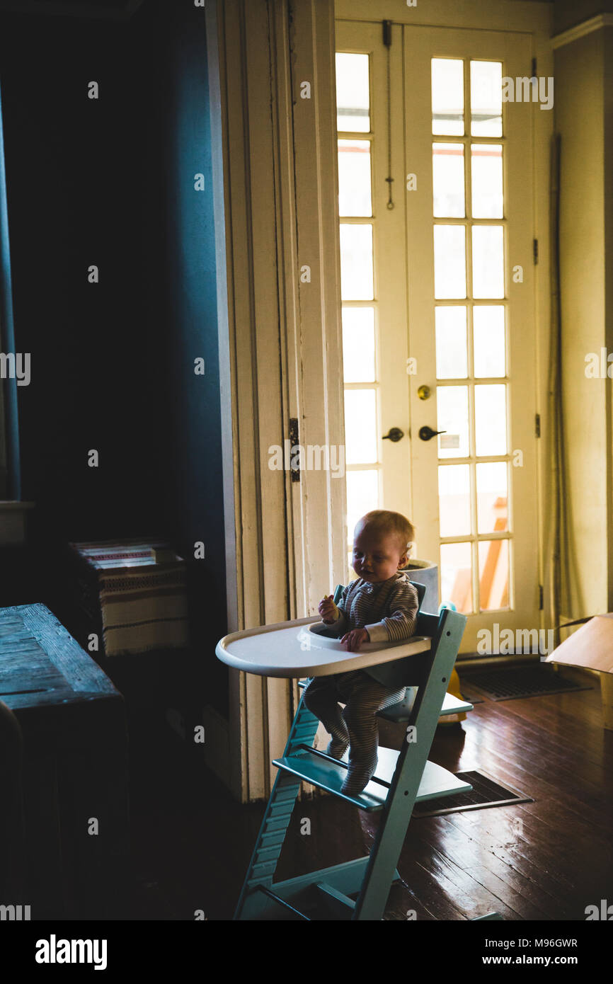 Baby sitting in high chair alone - Stock Image