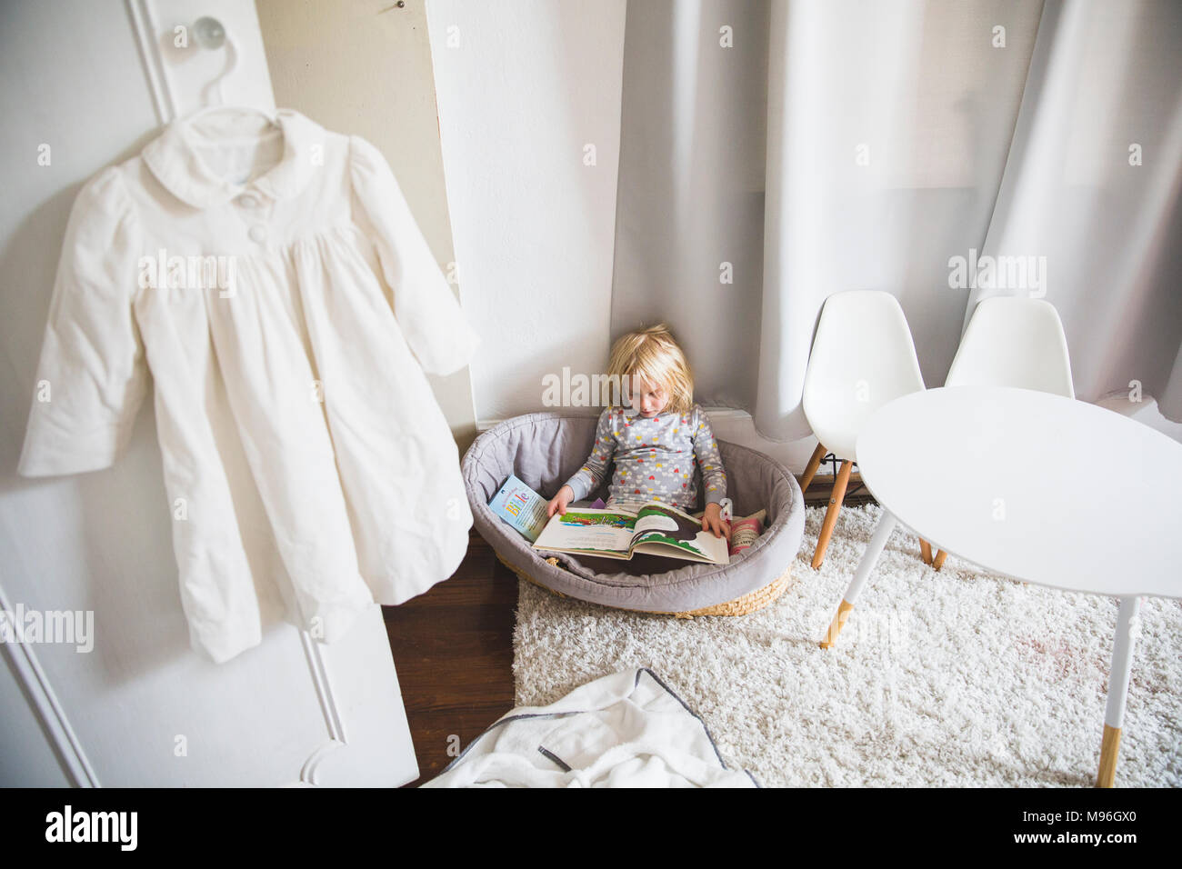 Girl sitting in playroom reading peacefully Stock Photo
