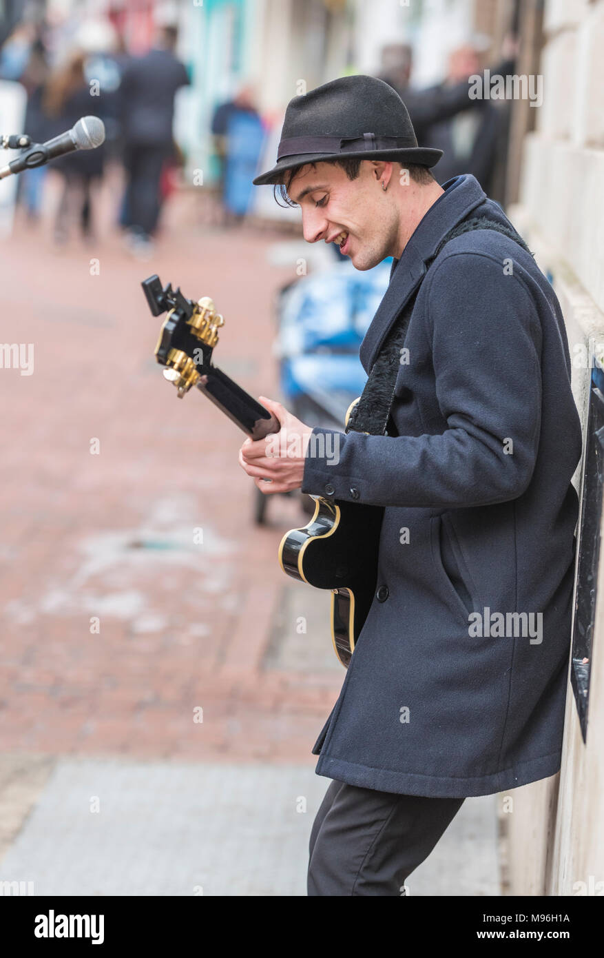 Portrait of a male street musician entertaining the public as the busker plays guitar in Brighton, East Sussex, England, UK. - Stock Image