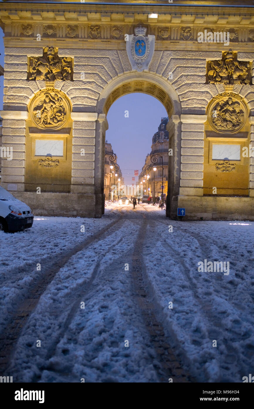 looking through the Porte de Peyrou in central Montpellier, France, at pedestrians walking in snow - Stock Image