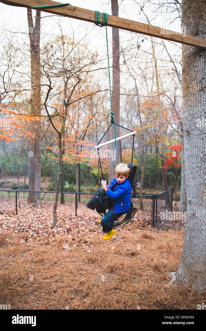 Boy in blue jacket swinging - Stock Image