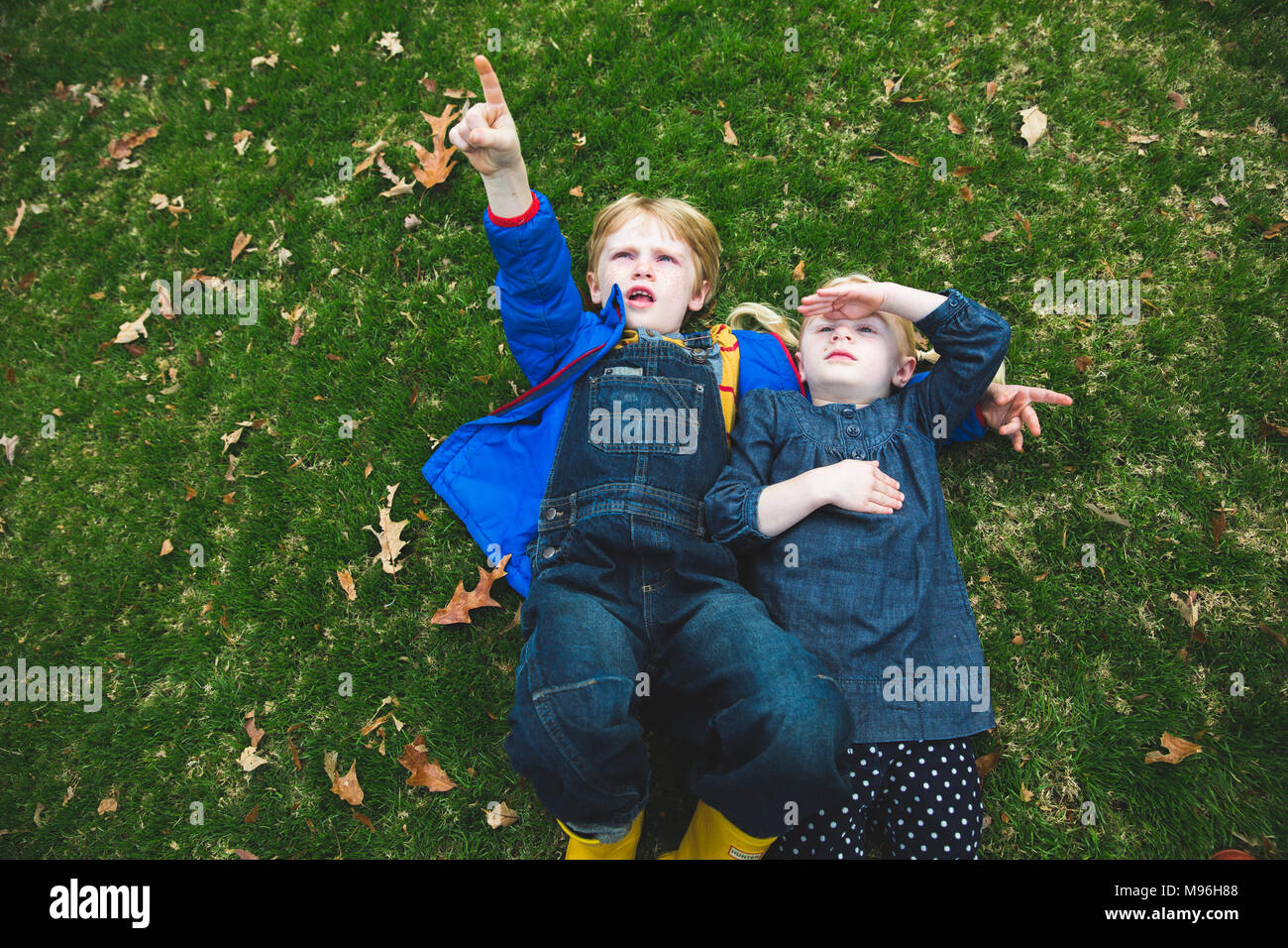Children laying down on grass - Stock Image