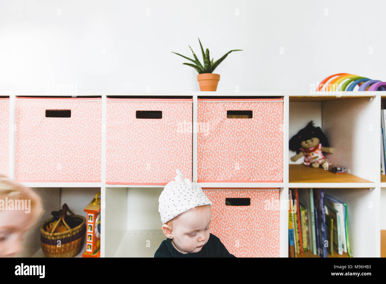 Girl in playroom sitting next to pink drawers - Stock Image