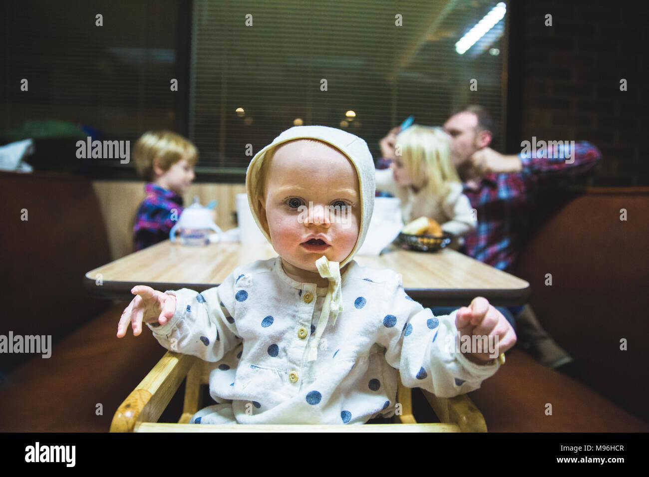 Baby looking at camera with family sat in diner booth behind - Stock Image