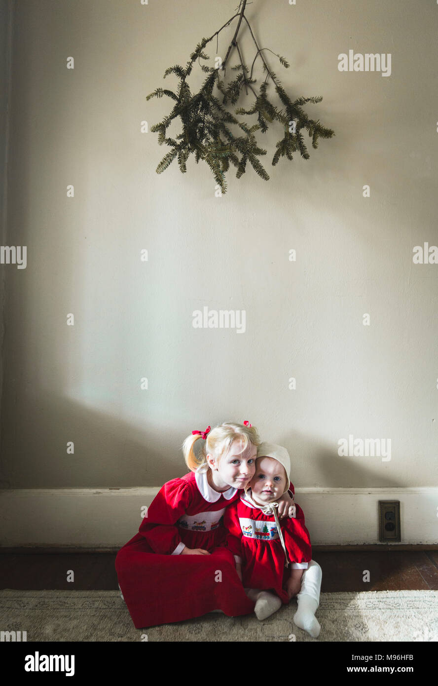 Girl and baby sitting on the floor beneath greenery - Stock Image