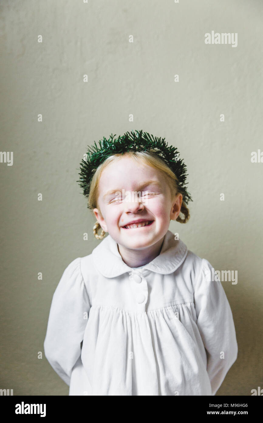 Girl smiling in white dress with wreath on her head - Stock Image