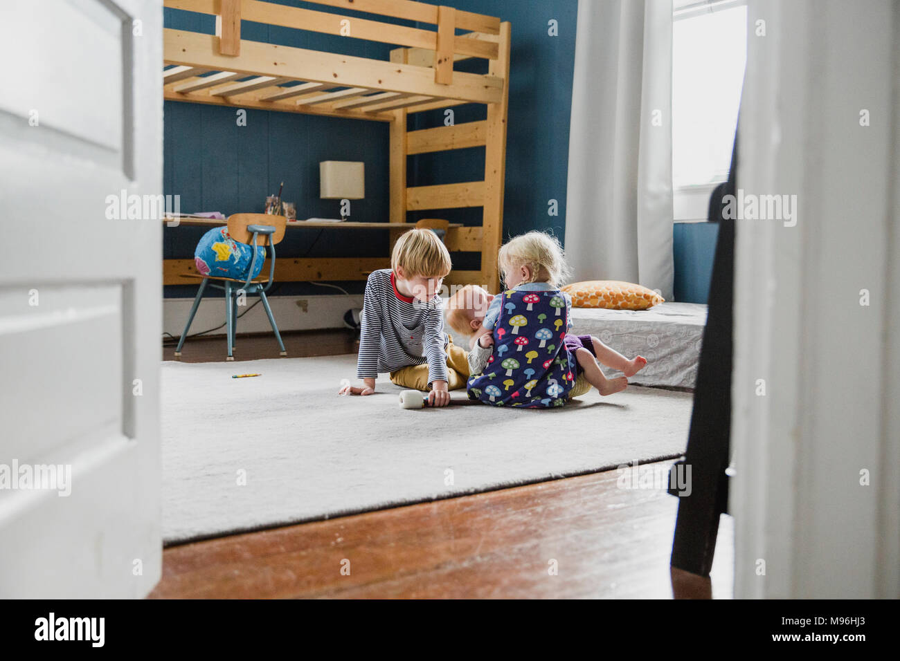 Two children and baby sitting in bedroom - Stock Image