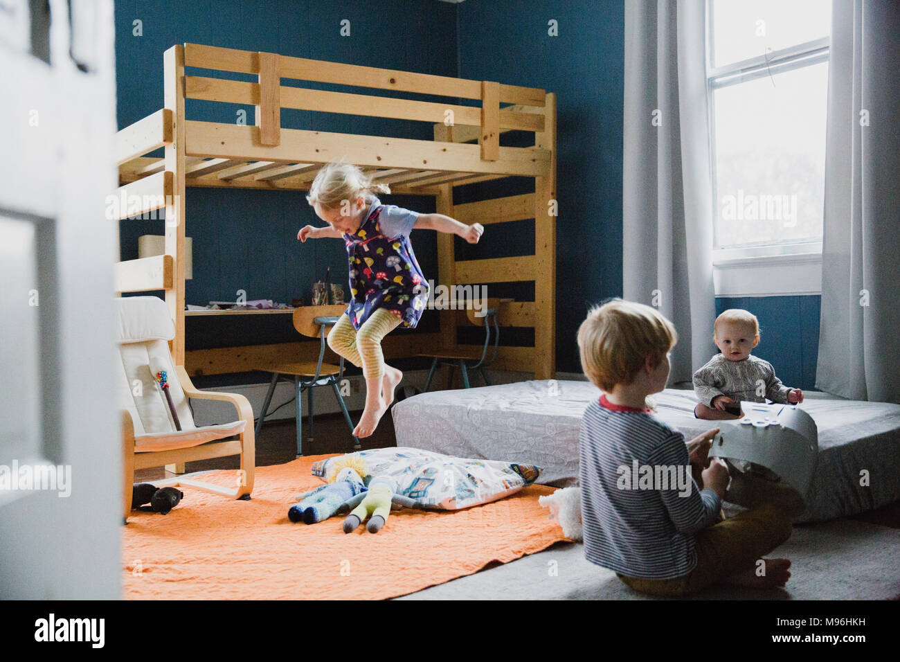 Girl jumping in bedroom next to two other children - Stock Image