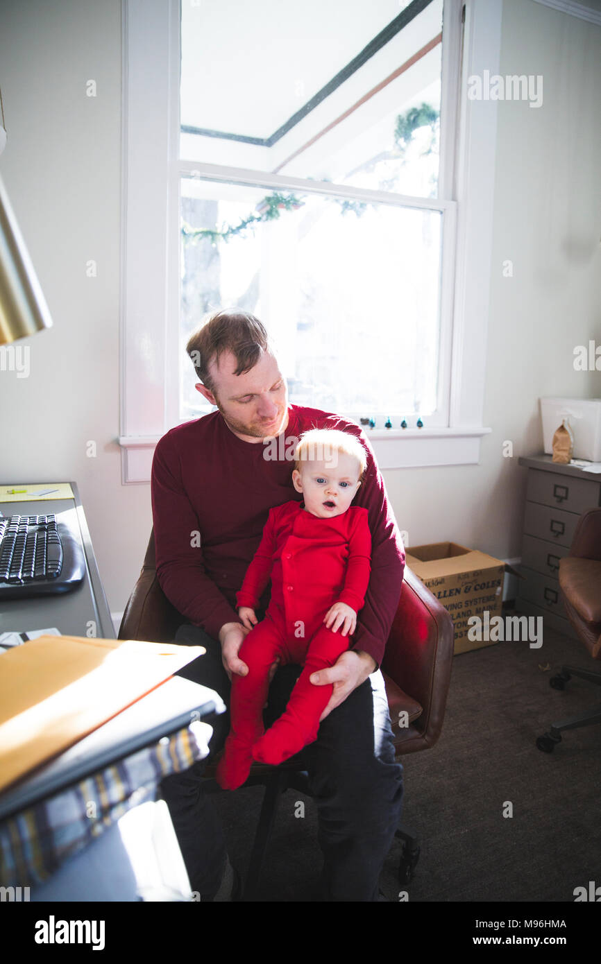 Father holding daughter whilst working from home - Stock Image