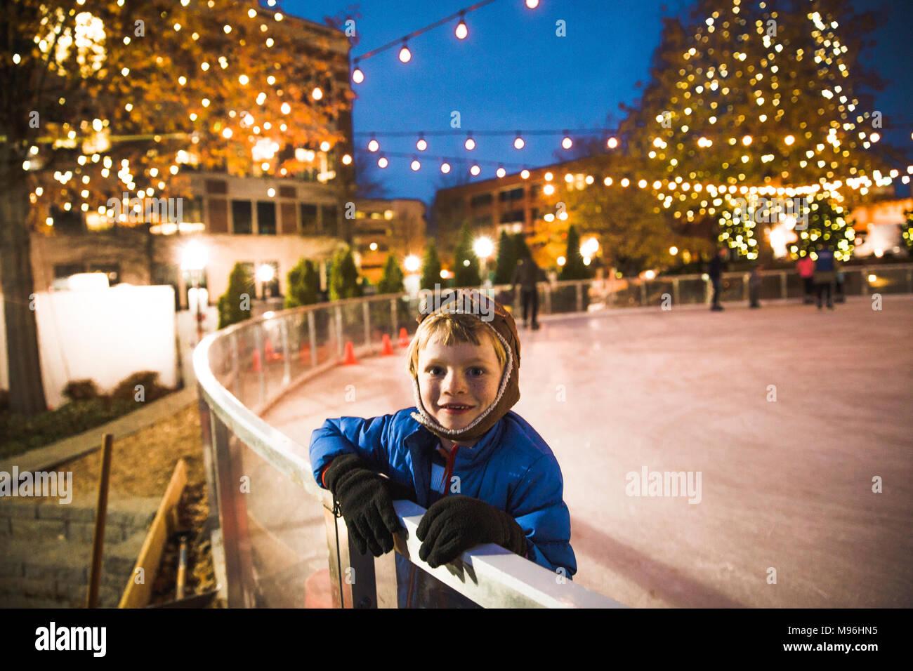 Boy looking at camera at the side of a skating rink - Stock Image