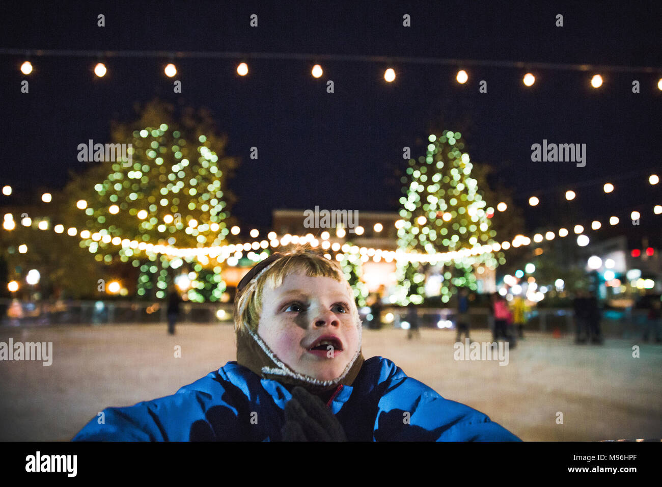 Boy looking up in wonder whilst on skating rink - Stock Image