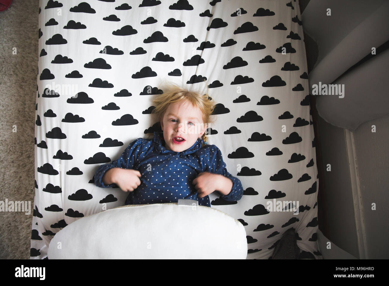 Girl laying on bed with cloud decal - Stock Image