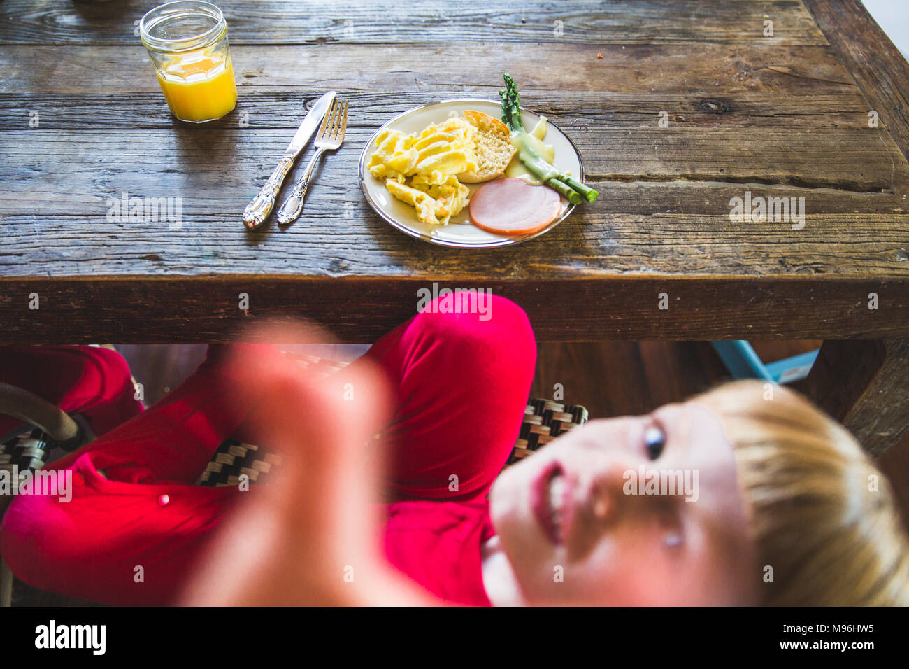 Boy looking up at camera with food ready on the table - Stock Image