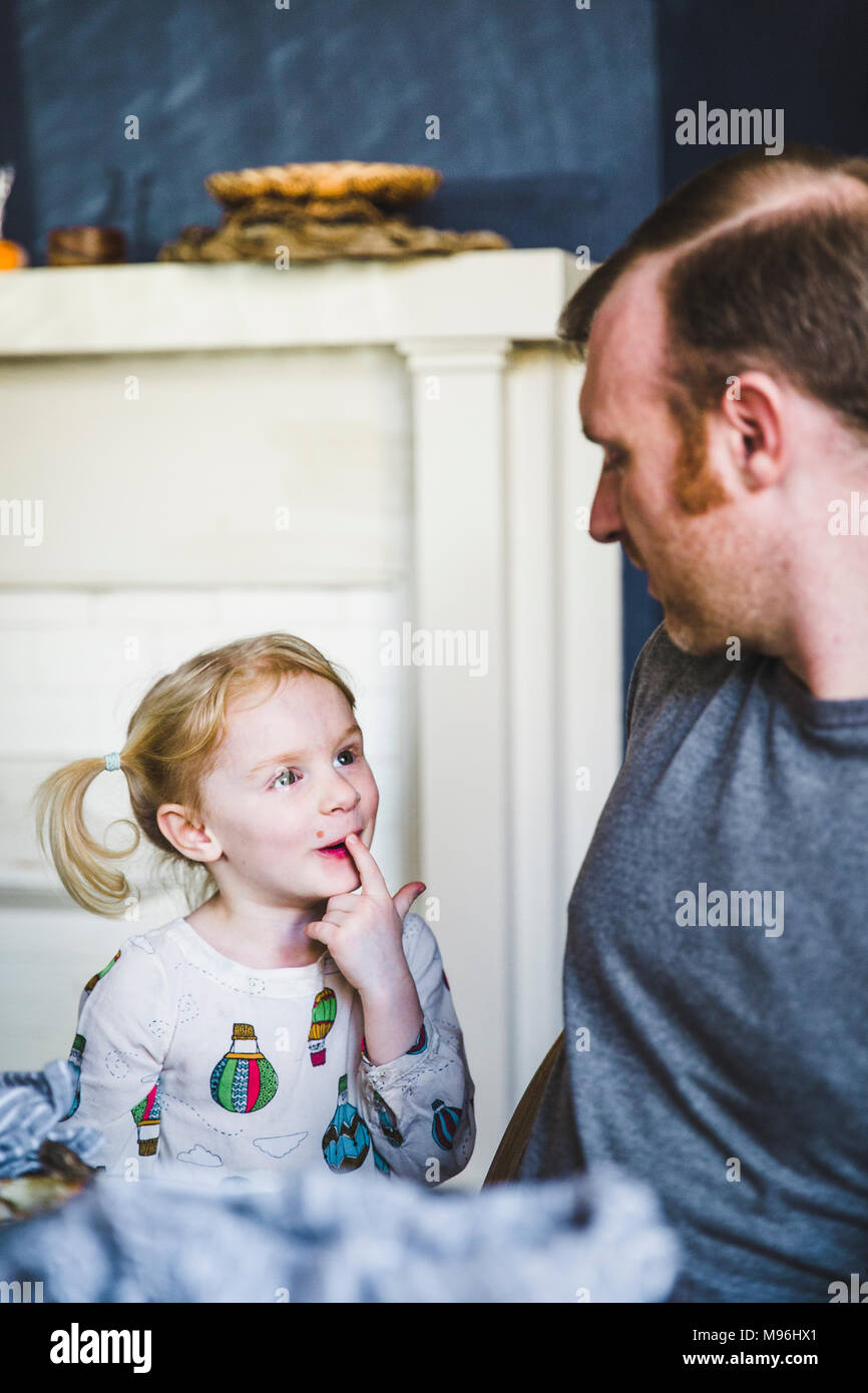 Girl and father looking at each other as girl points to her missing tooth - Stock Image