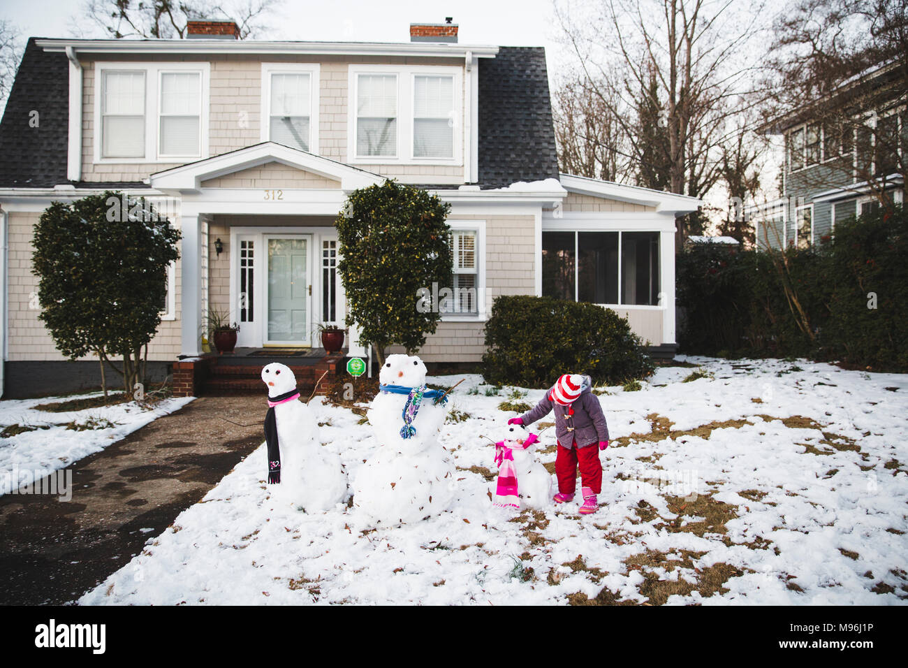 Girl standing next to line of three different snowman outside home - Stock Image