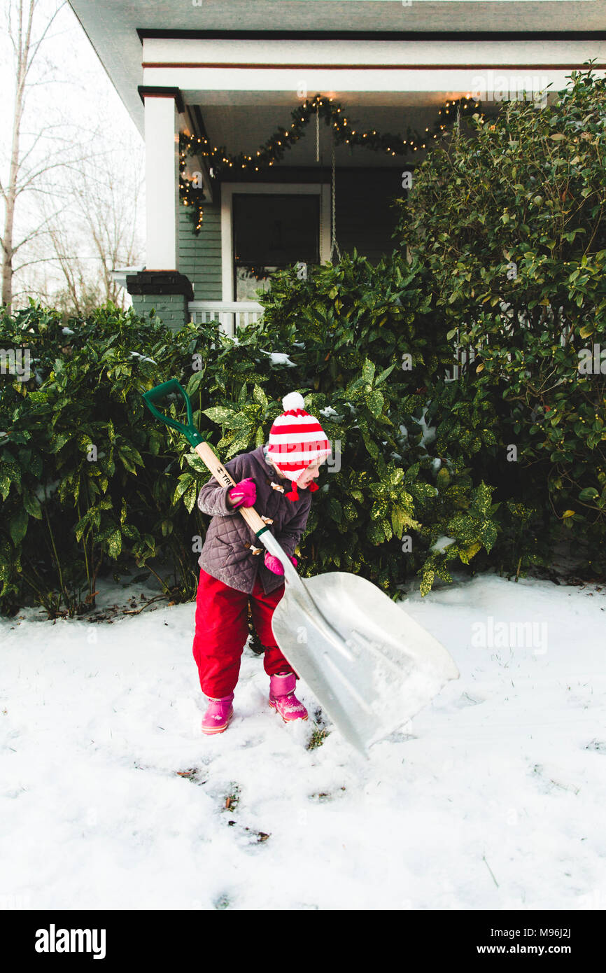Girl carrying large shovel moving snow - Stock Image