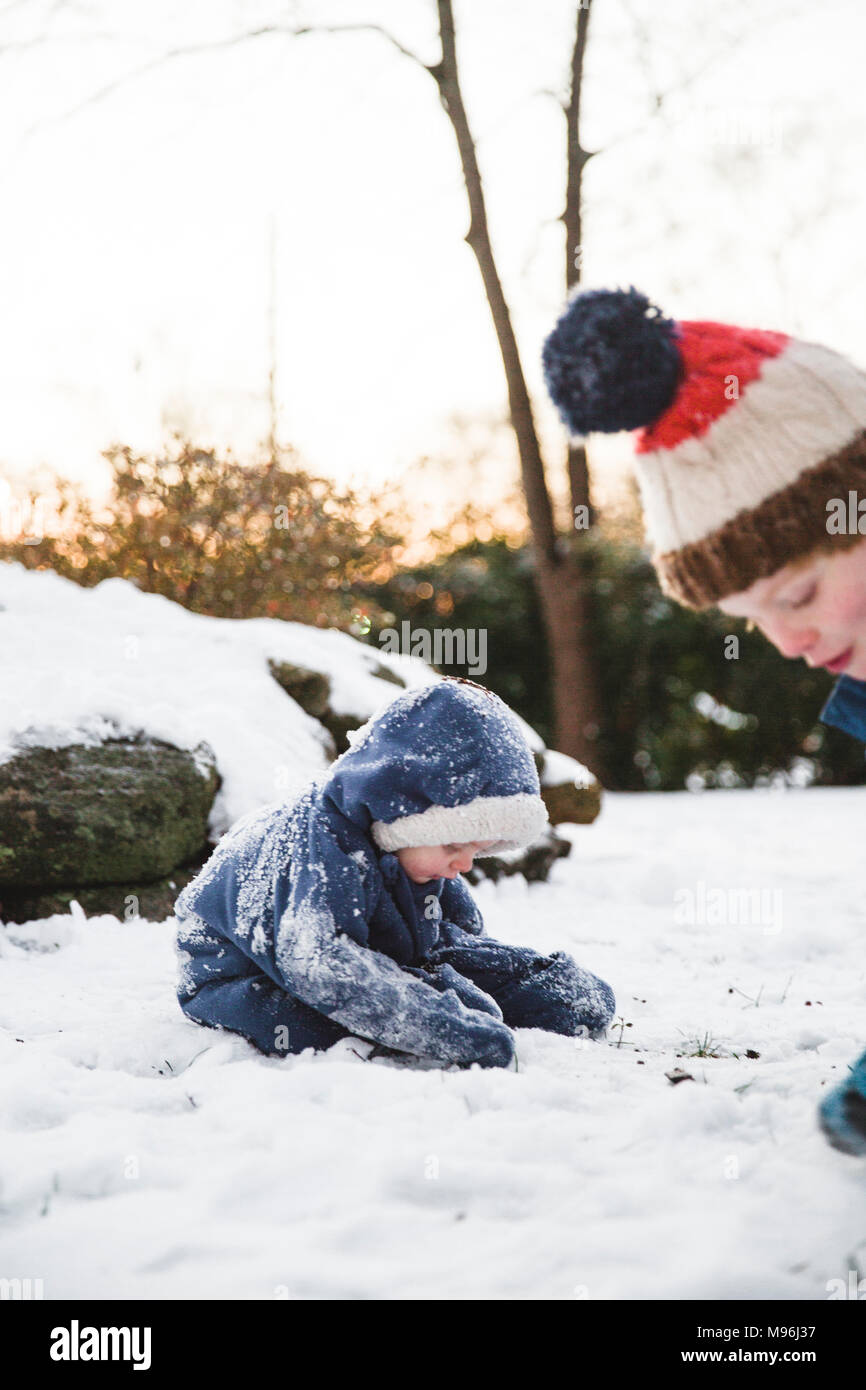 Two boys playing in the snow, making snowballs - Stock Image
