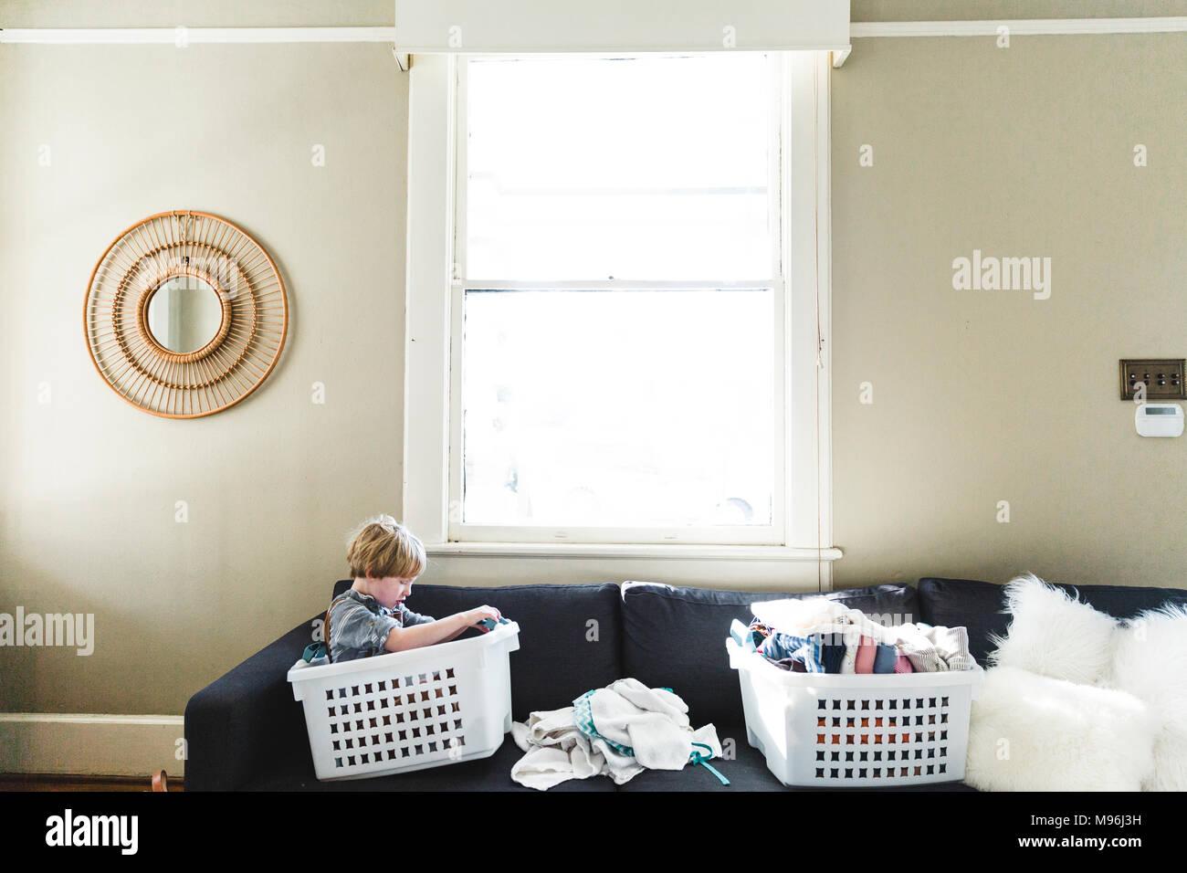 Boy sitting in laundry basket on sofa - Stock Image