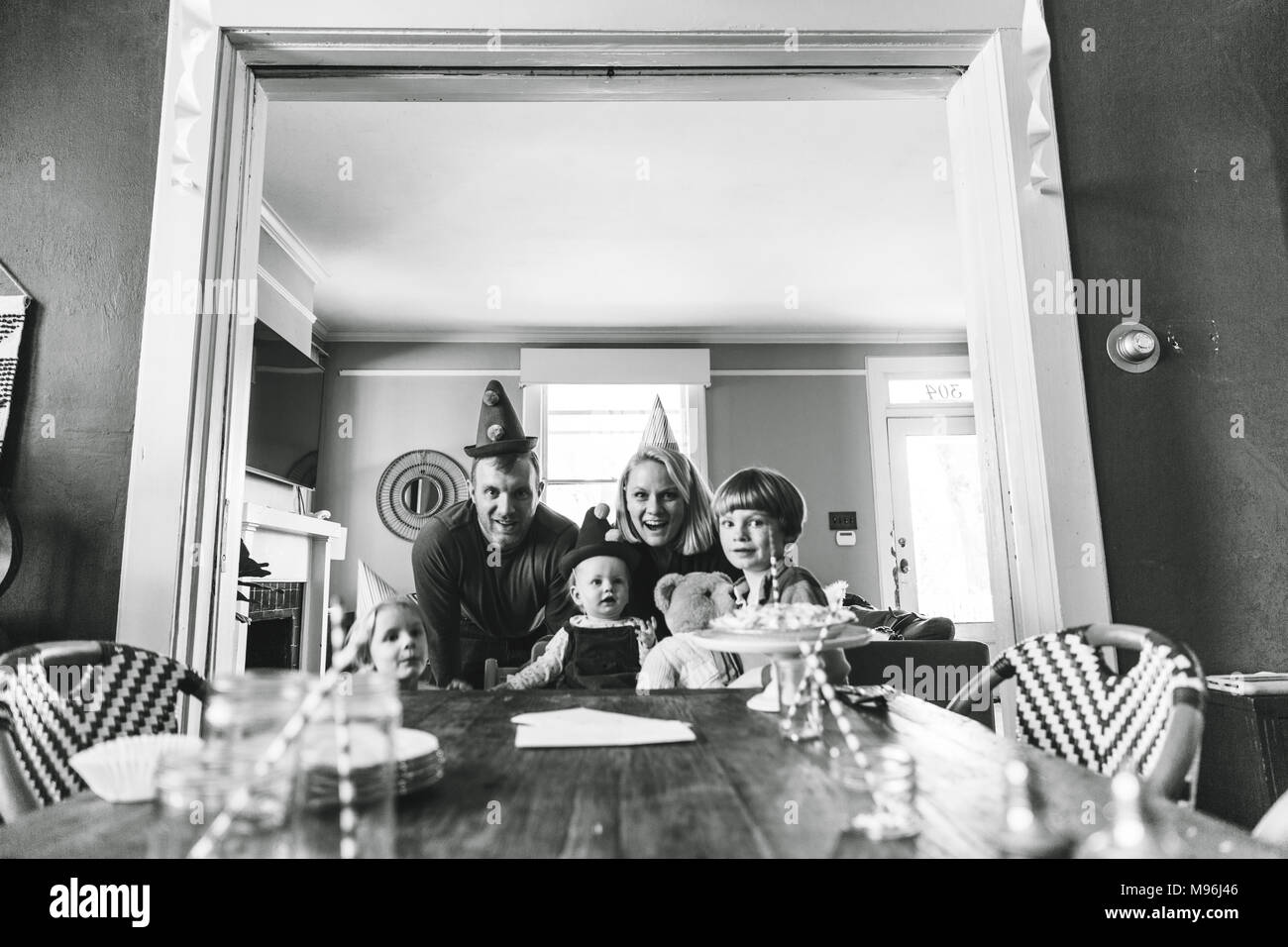 Family posing for photo at the end of table - Stock Image