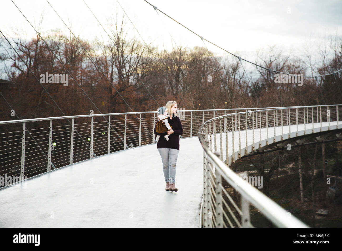 Woman holding child on a metal bridge - Stock Image