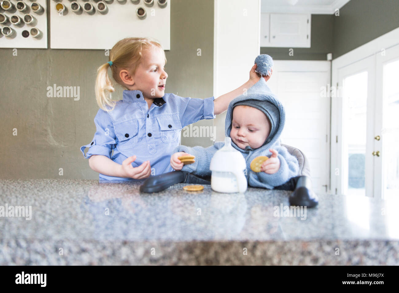 Girl and baby dressed in blue at kitchen counter - Stock Image