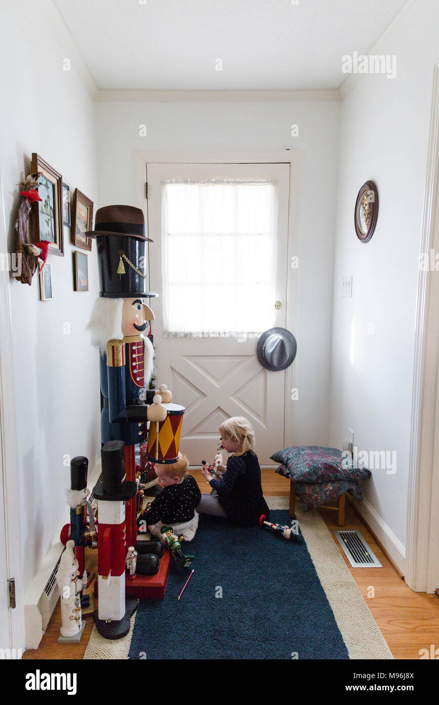 Girl and baby sitting in hallway next to nutcracker - Stock Image