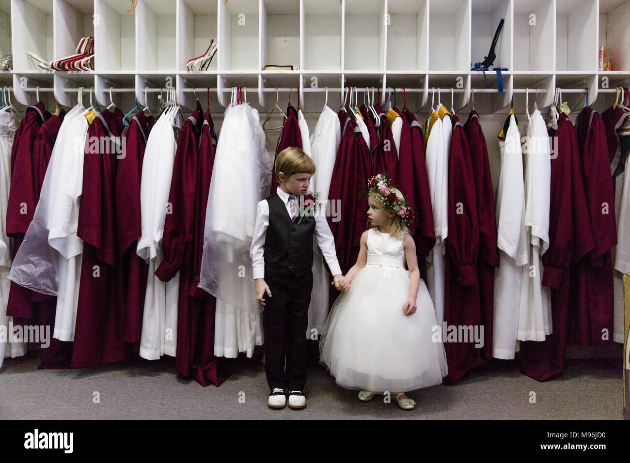 Boy and girl holding hands in front of choir robes - Stock Image