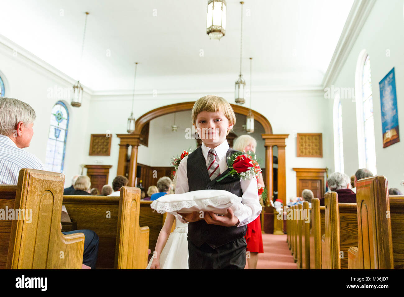Child ring bearer walking through church - Stock Image