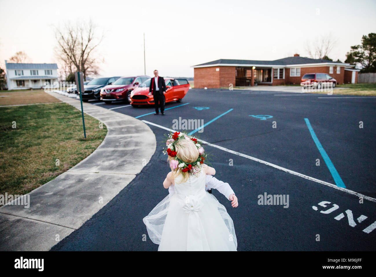 Girl in white dress in car park with flower wreath - Stock Image