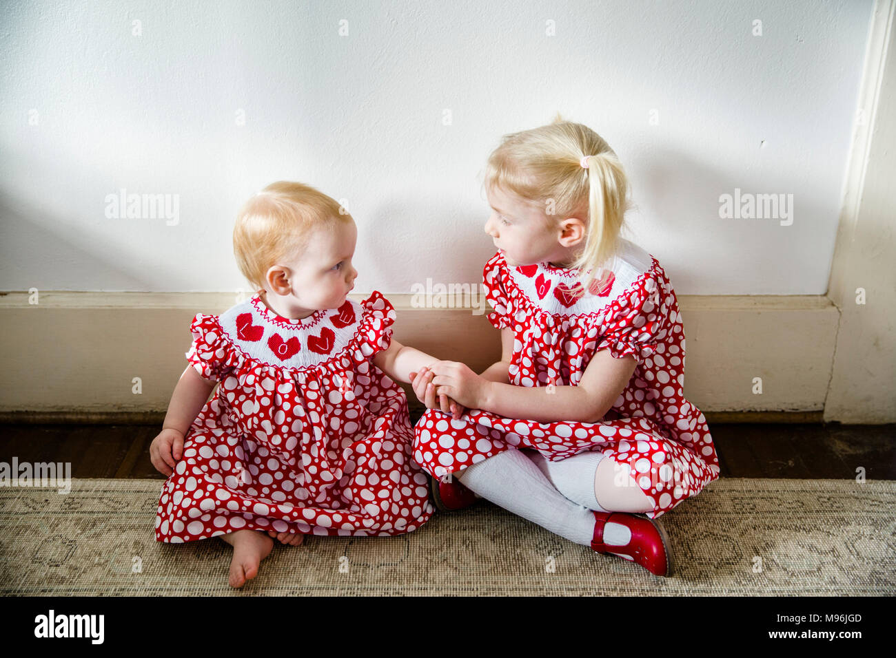 Baby and girl looking at each other in same red dress - Stock Image
