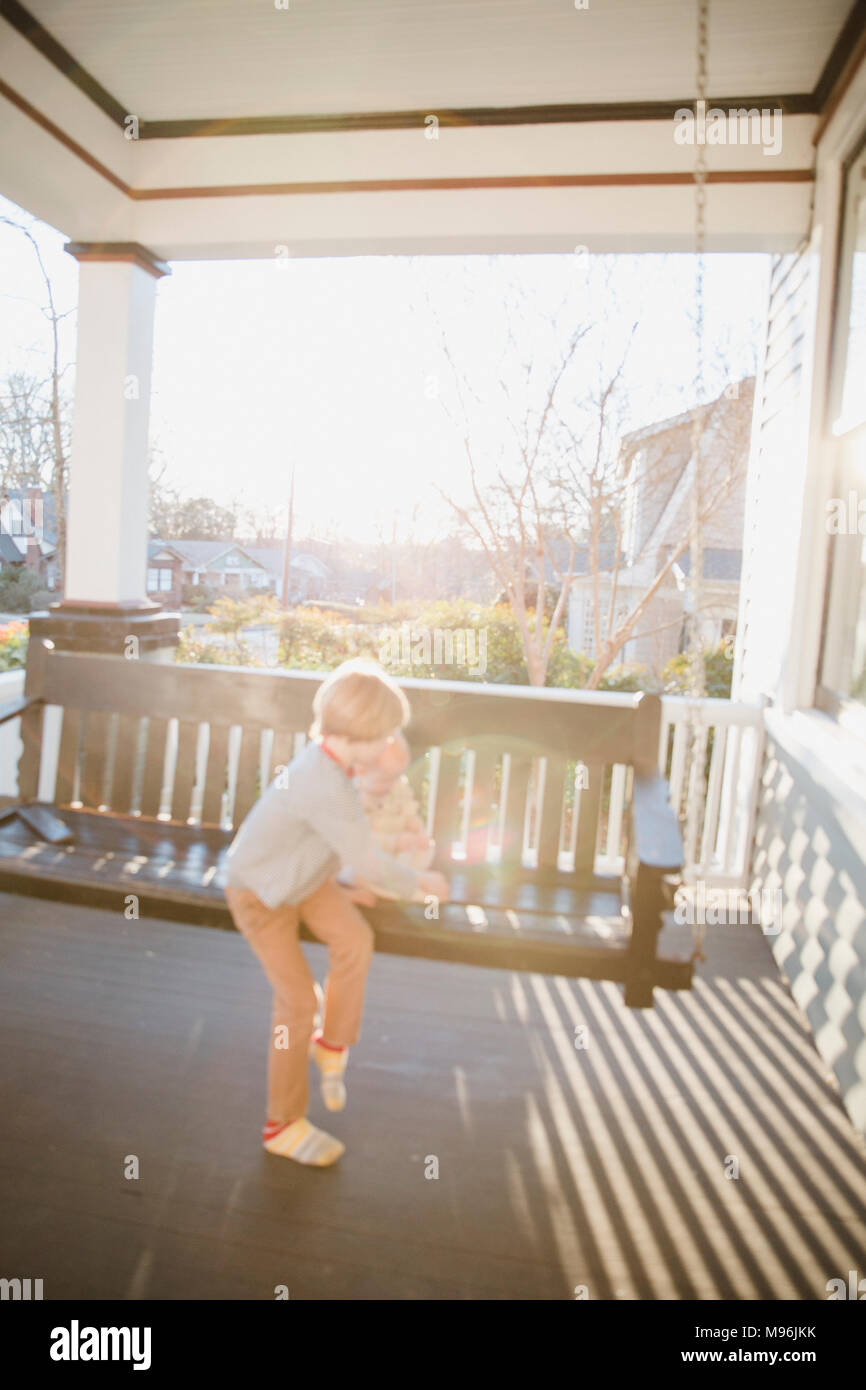 Baby and boy sitting on swinging bench - Stock Image